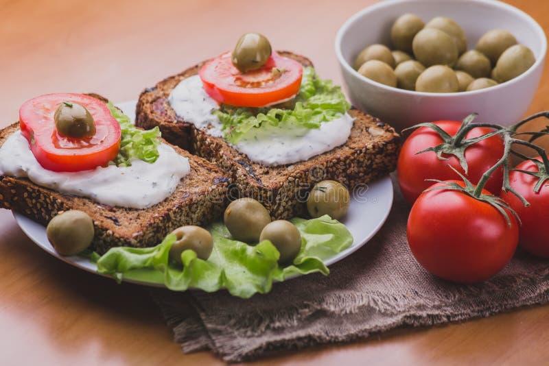 Bocadillos vegetarianos del pan hecho en casa con la salsa de queso o la crema, lechuga fotografía de archivo