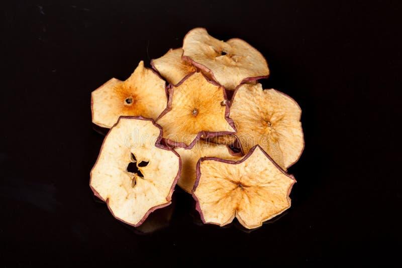 Bocado brillante, curruscante, quebradizo de la manzana madura y dulce en un fondo negro fotos de archivo