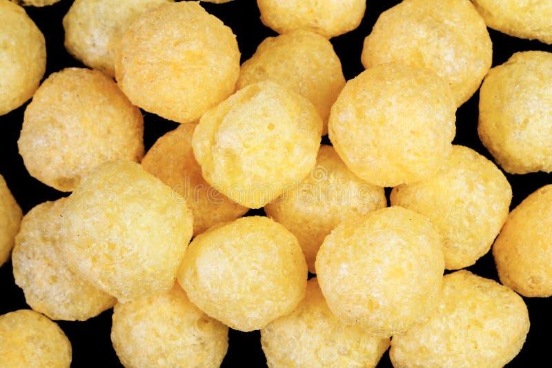 Bocado de las bolas del queso aislado sobre fondo negro La pila de queso condimentó las bolas sopladas crujientes aisladas Cierre fotos de archivo