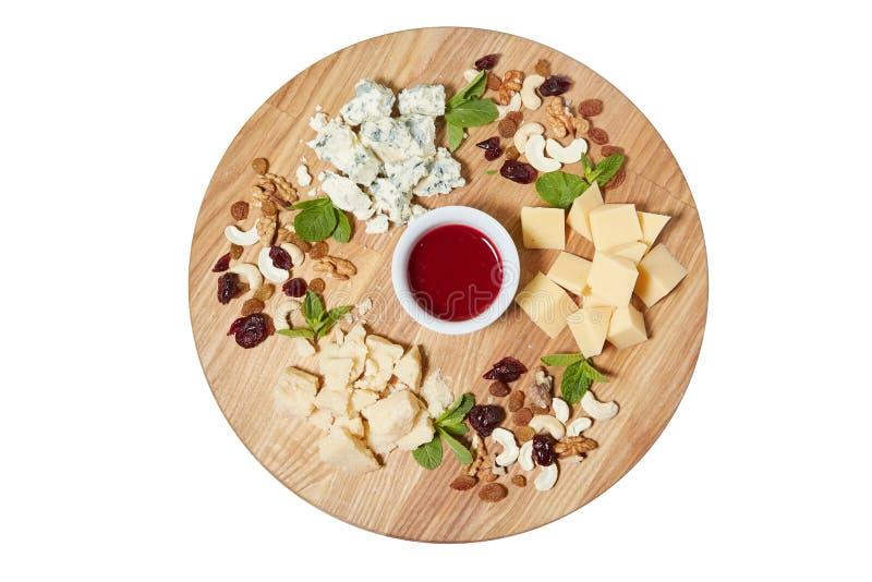 Bocado de los antipasti de la placa de queso con el queso italiano mezclado, anacardo, hojas de menta fresca imagen de archivo