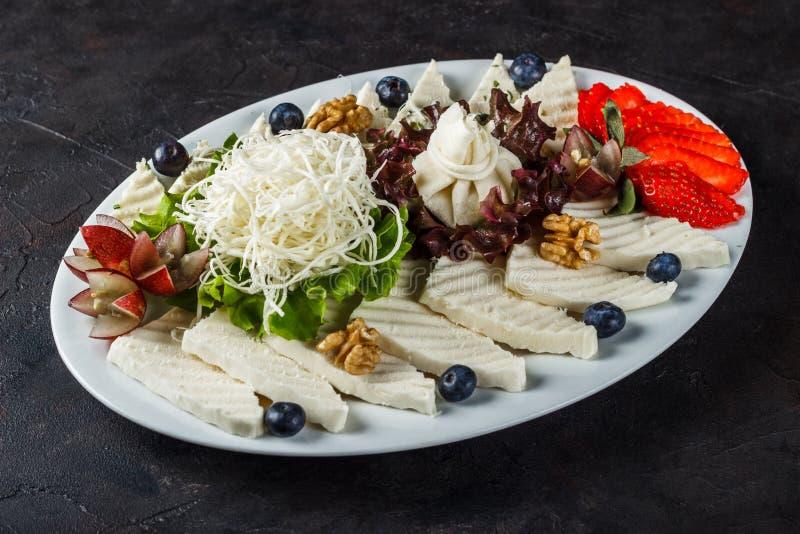 Bocado de los diversos quesos blancos, de los quesos, del brynza con las fresas y de los arándanos fotografía de archivo