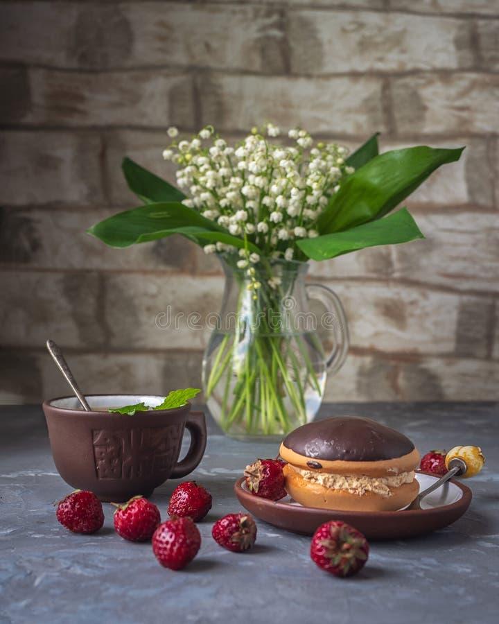 Bocado delicioso con las tortas y las fresas, un ramo de lirios del valle en un jarro de cristal fotografía de archivo libre de regalías