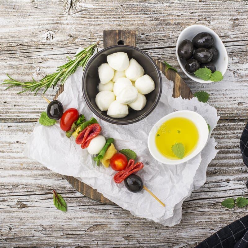 Bocado sano: kebabs apetitosos en una comida campestre con los tomates, mozzarella, salami, aceitunas negras, albahaca, tortellin foto de archivo