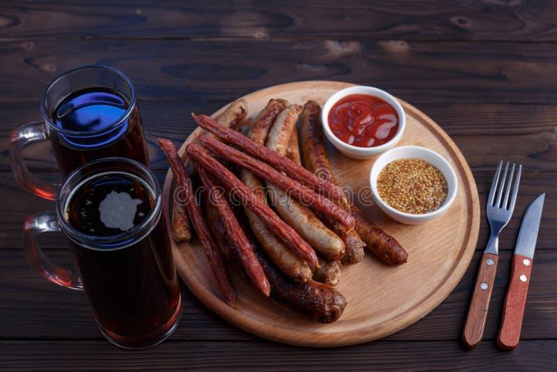 Bocados apetitosos de la cerveza, placa de la carne Opinión superior sobre la tabla con la parrilla foto de archivo libre de regalías