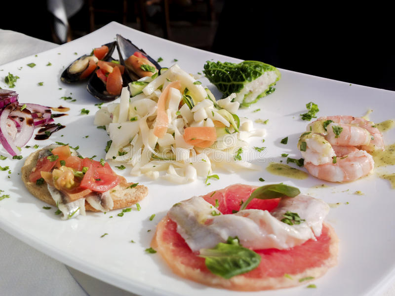 Bocados calientes y fríos de lapas, de pescados y del camarón Cocina mediterránea imagen de archivo