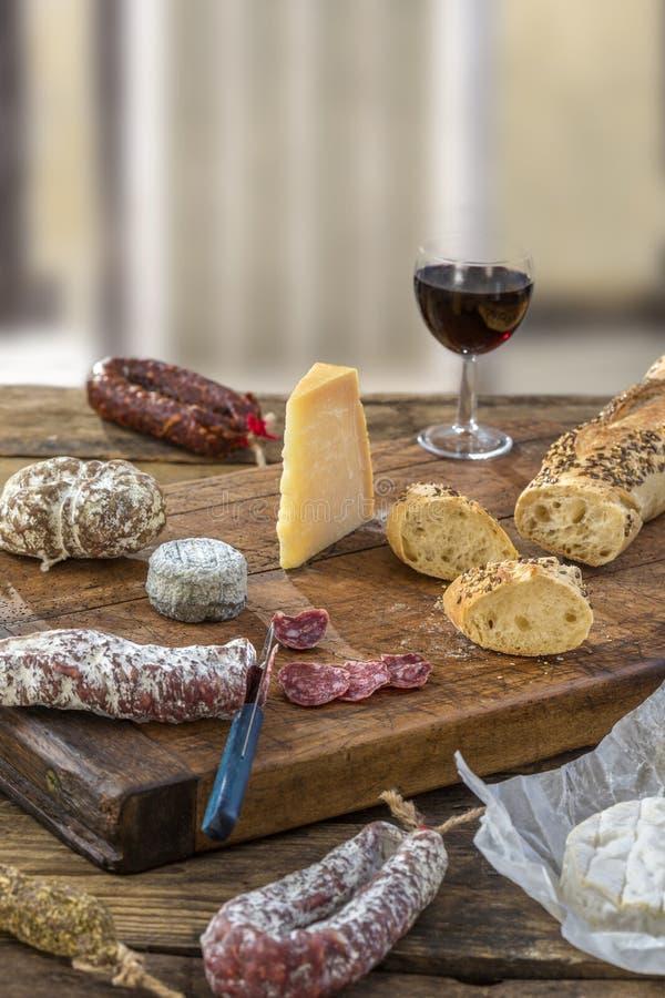 Bocados franceses con el vino - diversos tipos de quesos, pan, saussages secos, charcuterie, vid roja en un fondo gris imagen de archivo