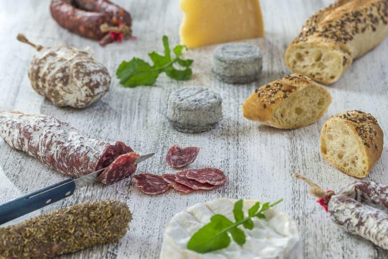 Bocados franceses con el vino - diversos tipos de quesos, pan, saussages secos, charcuterie, vid roja en un fondo gris fotografía de archivo libre de regalías
