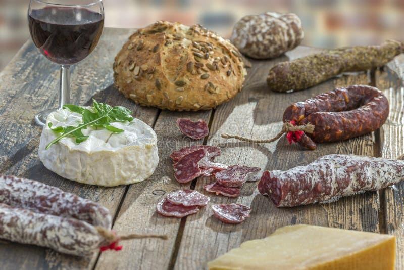 Bocados franceses con el vino - diversos tipos de quesos, pan, saussages secos, charcuterie, vid roja en un fondo gris imágenes de archivo libres de regalías