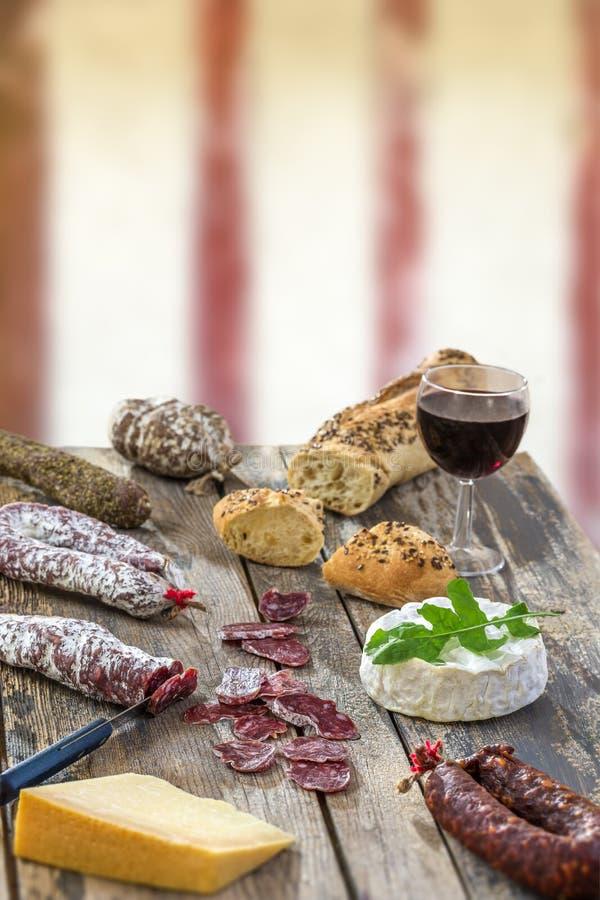 Bocados franceses con el vino - diversos tipos de quesos, pan, suassages secos, charcuterie, vid roja en un fondo gris fotos de archivo