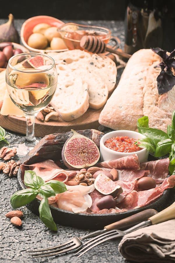 Bocados italianos del vino de los antipasti fijados imagen de archivo