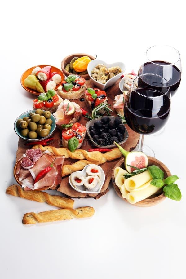 Bocados italianos del vino de los antipasti fijados Variedad del queso, aceitunas mediterráneas, salmueras, di Parma, tomates, al fotografía de archivo libre de regalías