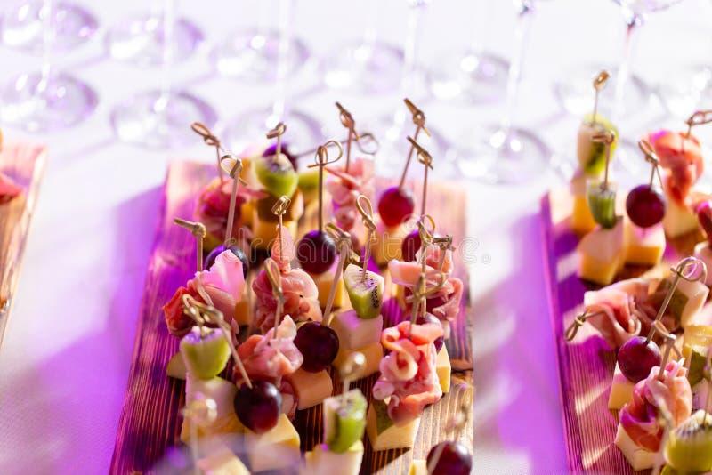 Bocados ligeros en una placa en una tabla de comida fría Mini canapes, delicadezas y bocados clasificados, comida del restaurante foto de archivo