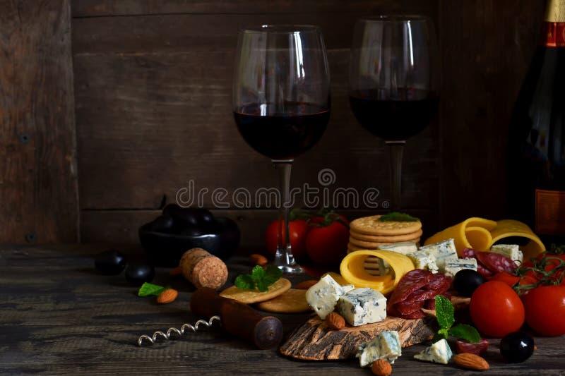 Bocados para el vino: queso verde, aceitunas, salami delicadezas fotografía de archivo