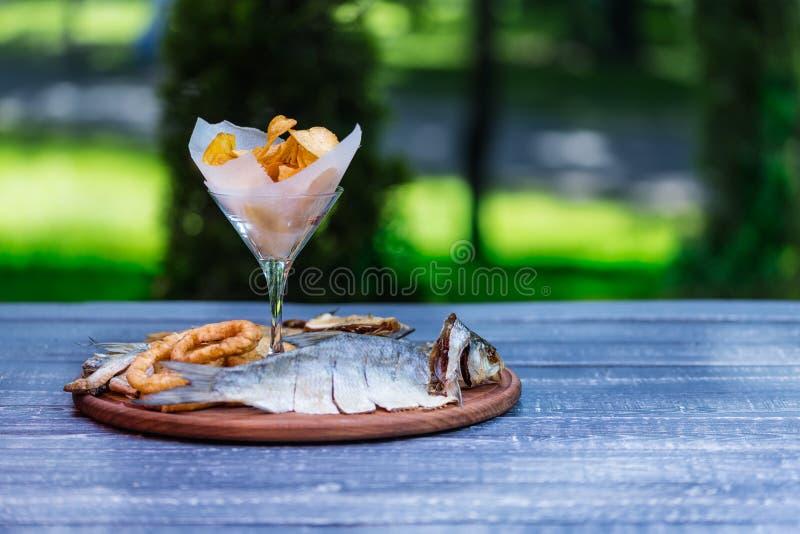 Bocados para la cerveza Patatas saladas, secadas de los pescados, del anillo del calamar y fritas, en la tabla de cortar y el fon fotografía de archivo