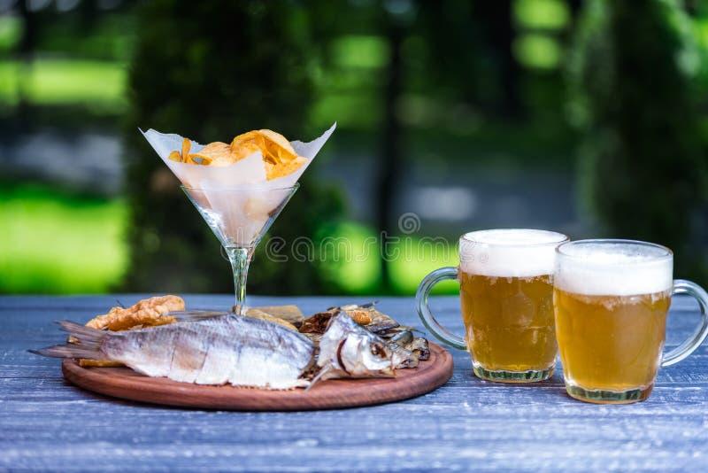 Bocados para la cerveza y dos tazas de cerveza Patatas saladas, secadas de los pescados, del anillo del calamar y fritas, en la t foto de archivo