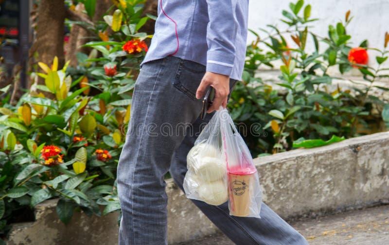 Bocados que llevan del hombre de Yuong del café y del pan en bolsos que hacen compras plásticos desechables fotografía de archivo libre de regalías