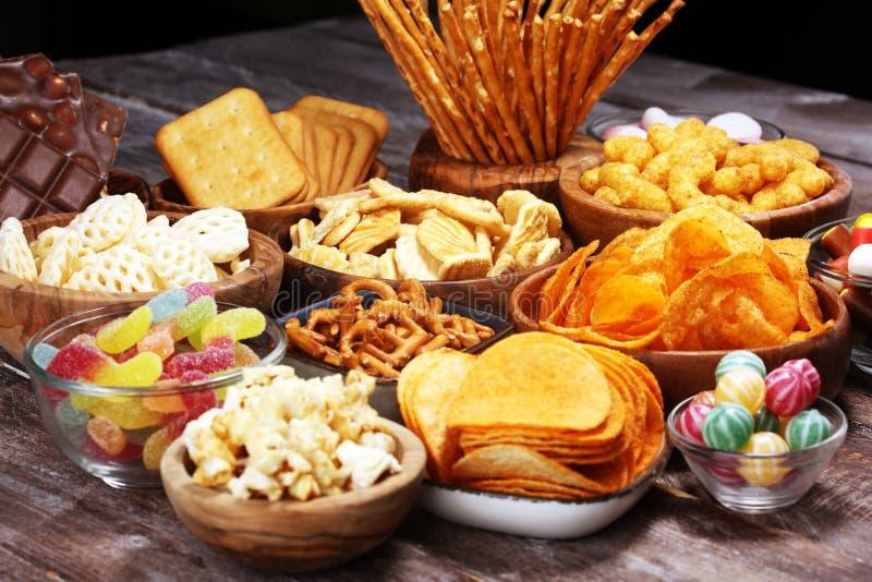 Bocados salados Pretzeles, microprocesadores, galletas en cuencos de madera en la tabla fotografía de archivo