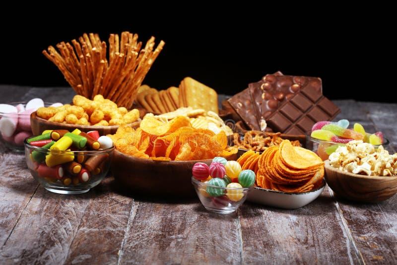 Bocados salados Pretzeles, microprocesadores, galletas en cuencos de madera en la tabla imagen de archivo libre de regalías