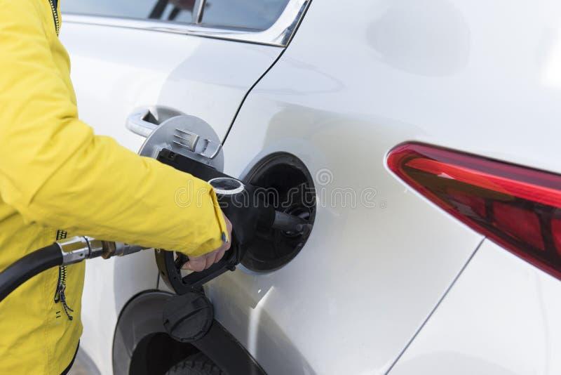 Bocal de combustível do close-up com posse da mão Encha acima o combustível no statio do gás foto de stock