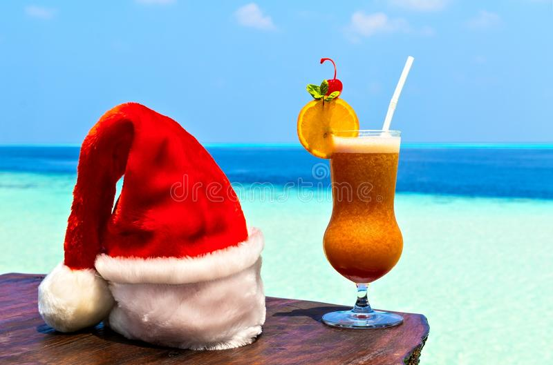 Bocal of drink is on a beach table with Santa hat royalty free stock image