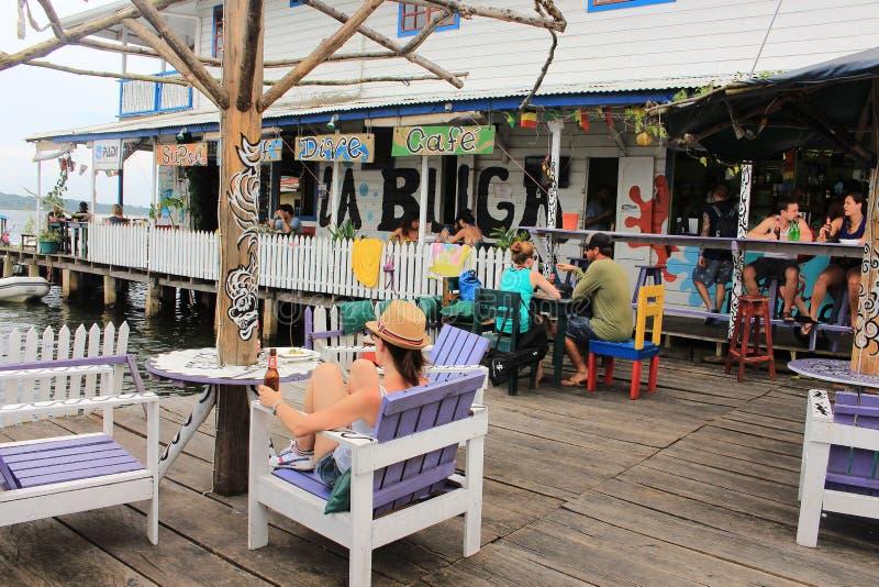 Bocas del Toro, Panamà ¡ - Augusti, 10th av 2014: Turister och handelsresande tycker om en drink på stänger för strand för den Bo royaltyfria foton