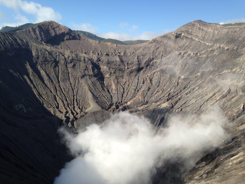 Bocca del vulcano di fumo pericolosa, paesaggio del ` s della montagna, cielo blu, scogliere fotografia stock