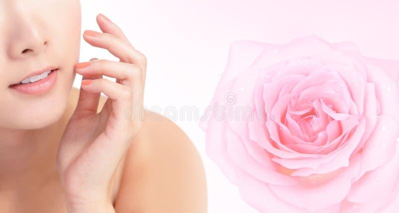 Bocca di sorriso della giovane donna con il fiore di rosa di colore rosa fotografia stock libera da diritti
