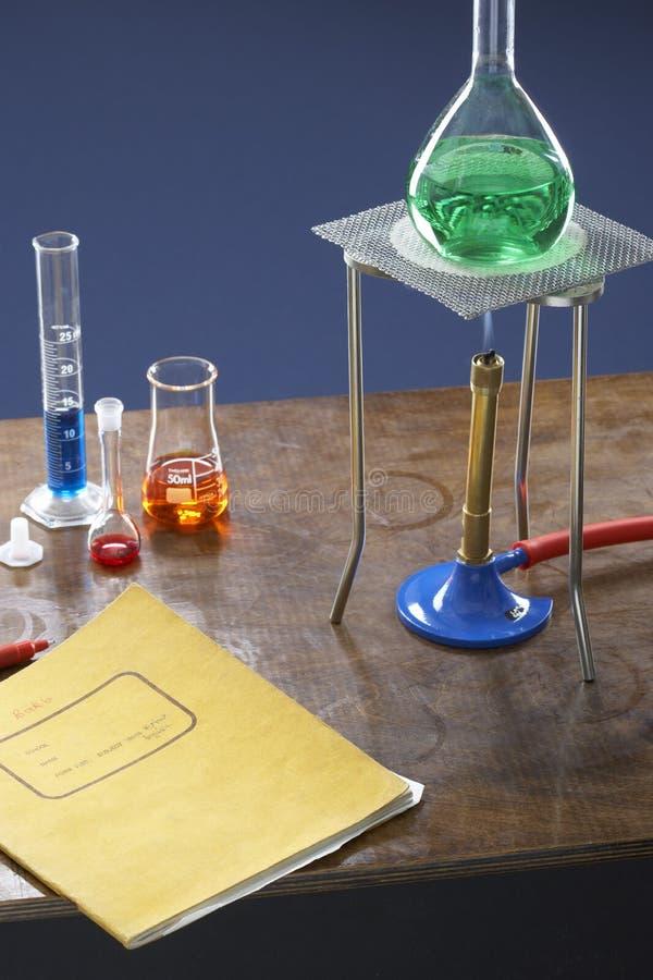 Boccetta del treppiede del becco Bunsen e provette nel laboratorio di scienza immagini stock libere da diritti