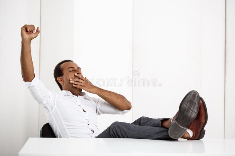 Bocejo africano bem sucedido novo sonolento do homem de negócios, sentando-se no local de trabalho fotografia de stock