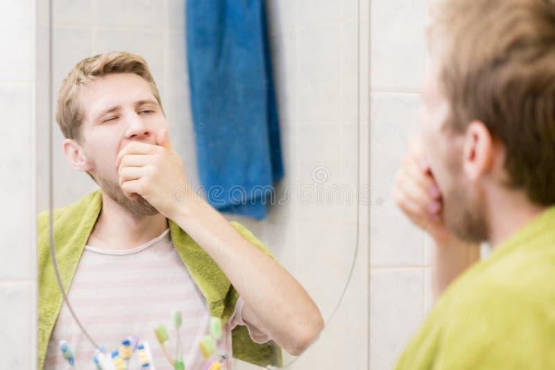 Bocejo farpado novo do homem na frente do espelho no banheiro fotos de stock royalty free