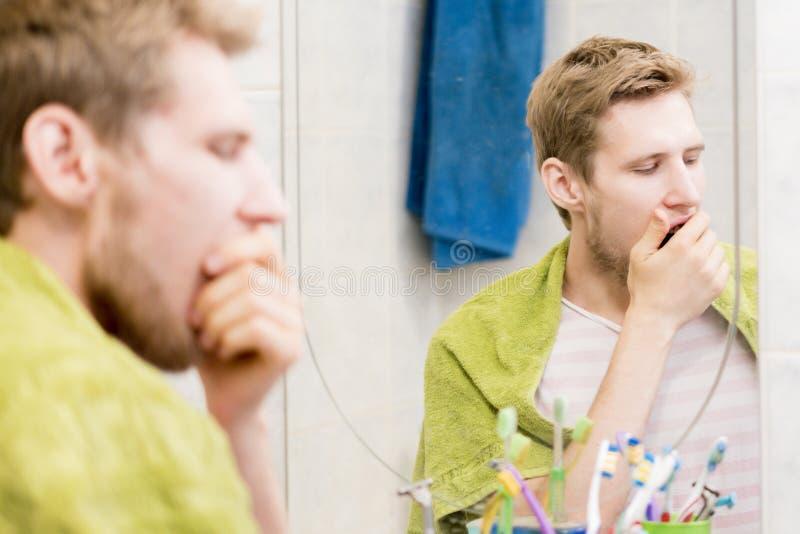 Bocejo farpado novo do homem na frente do espelho no banheiro imagem de stock royalty free