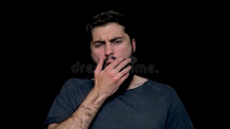 Bocejo farpado novo sonolento do homem, fechando sua boca com a mão, isolada no fundo Vista de bocejo do indivíduo farpado imagem de stock royalty free