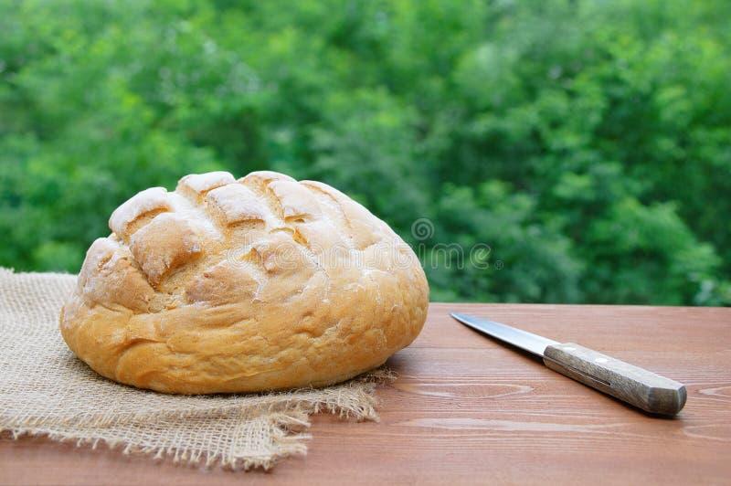 Bochenek pszeniczny chleb i nóż Na brown drewnianym tle na na wolnym powietrzu fotografia stock