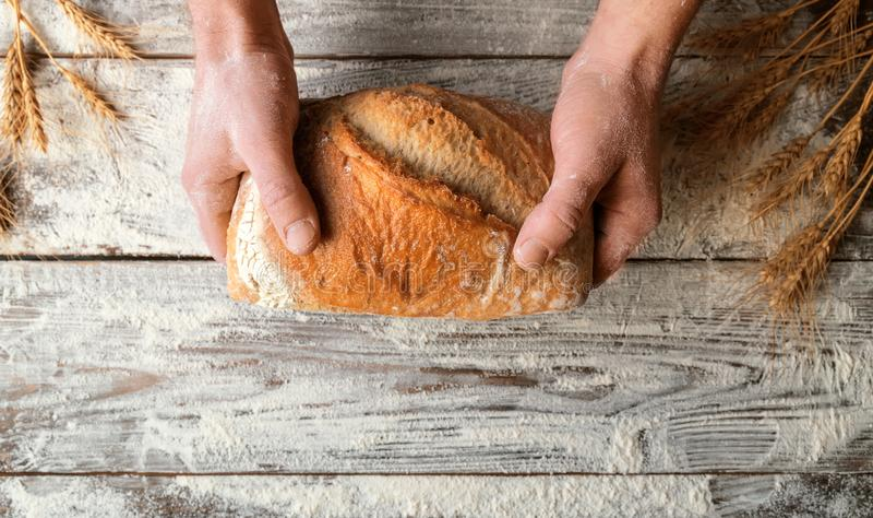 Bochenek pszeniczny chleb w mężczyzna rękach obraz royalty free