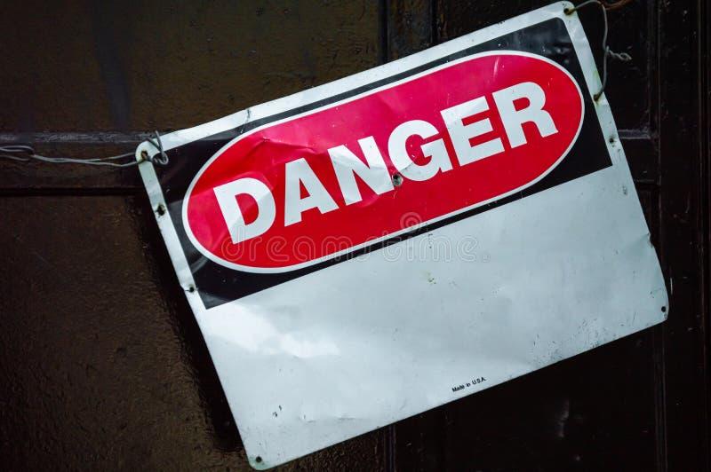 Bochtig oud metaalwaarschuwingsbord dat GEVAAR leest De ruimte van het exemplaar stock foto