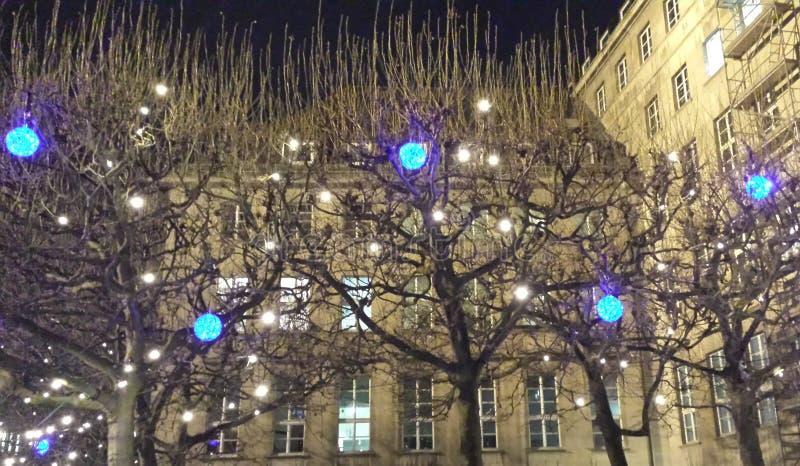 Bochum Tyskland - December 12, 2016: Blåa och vita LEDDE lampor på träden på bakgrunden av stadshuset Bochum royaltyfri fotografi