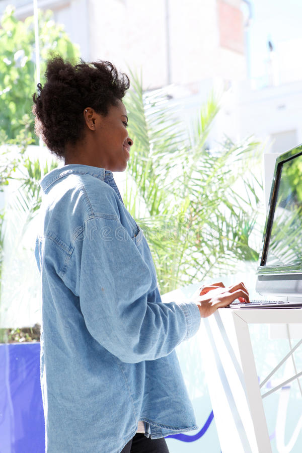 Bocznego portreta amerykanina afrykańskiego pochodzenia młoda kobieta pracuje na laptopie zdjęcia stock