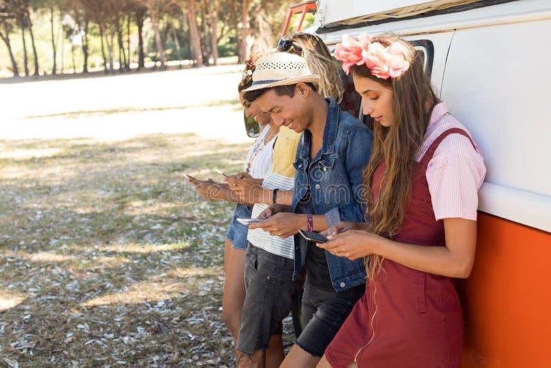 Bocznego widoku belzebuby używa telefon komórkowego podczas gdy stojący obozowicza samochodem dostawczym obraz stock