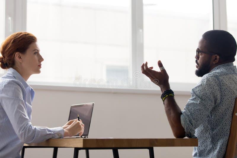 Bocznego widoku bizneswoman i biznesmen negocjuje siedzieć w b zdjęcie stock