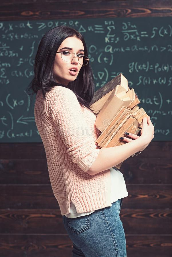Bocznego widoku brunetki szkoły wyższej dziewczyny przewożenia seksowny rozsypisko książki Mądrze żeński uczeń w szkłach iść bibl zdjęcia stock