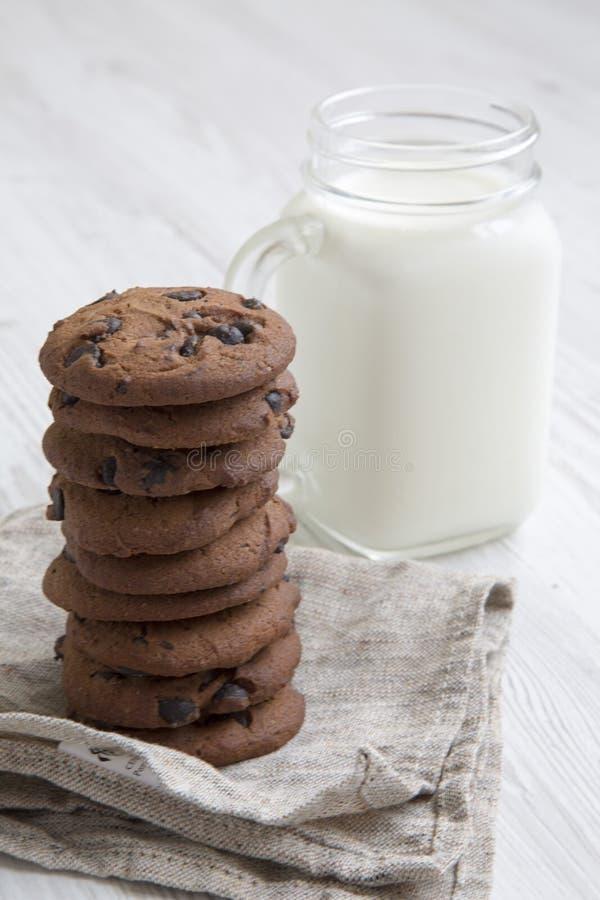 Bocznego widoku czekoladowego układu scalonego ciastka z mlekiem na białym drewnianym stole fotografia stock