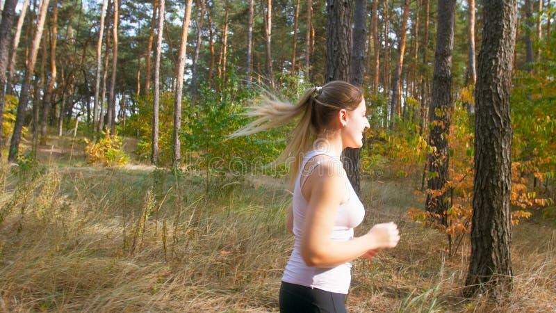 Bocznego widoku fotografia młoda msiling kobieta jogging w lesie przy słonecznym dniem zdjęcie royalty free