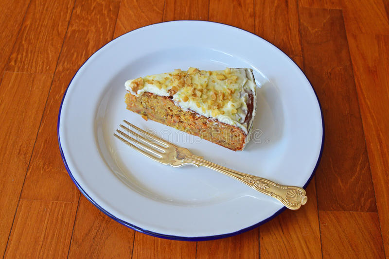 Bocznego widoku kąt Marchwiany tort słuzyć na klasycznym enamelware z srebną łyżką zdjęcia royalty free