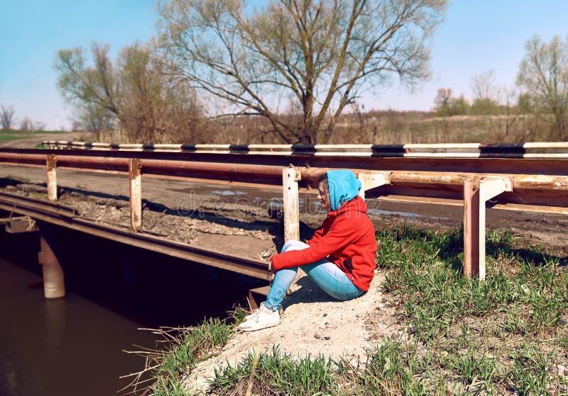 Bocznego widoku kobiety smutny złowrogi obsiadanie przy mostem obok rzeki Młoda dziewczyna patrzeje puszek z przykrością zdjęcie stock