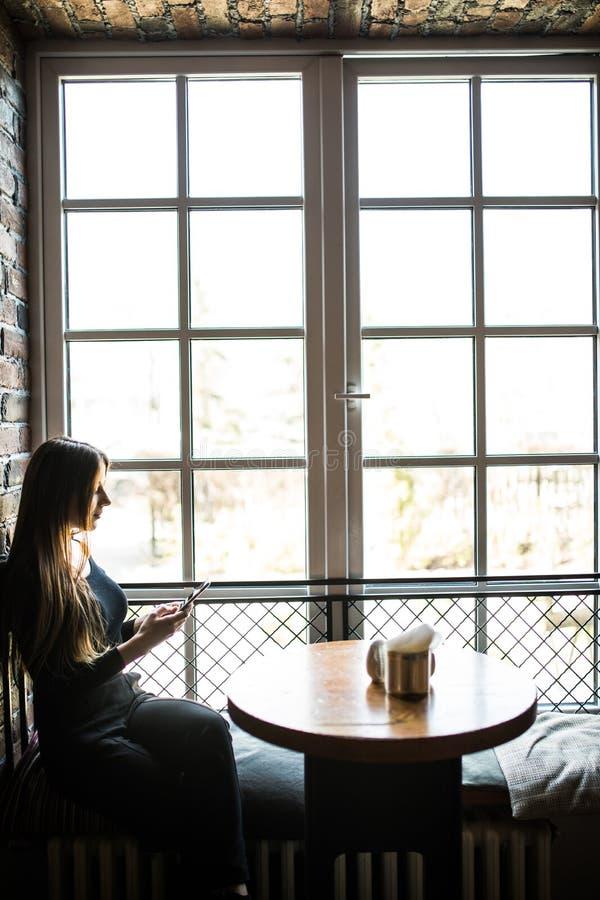 Bocznego widoku młoda kobieta siedzi w kawiarni przy drewnianym stołem przed okno i używa smartphone Dziewczyn spojrzenia przy ek fotografia stock