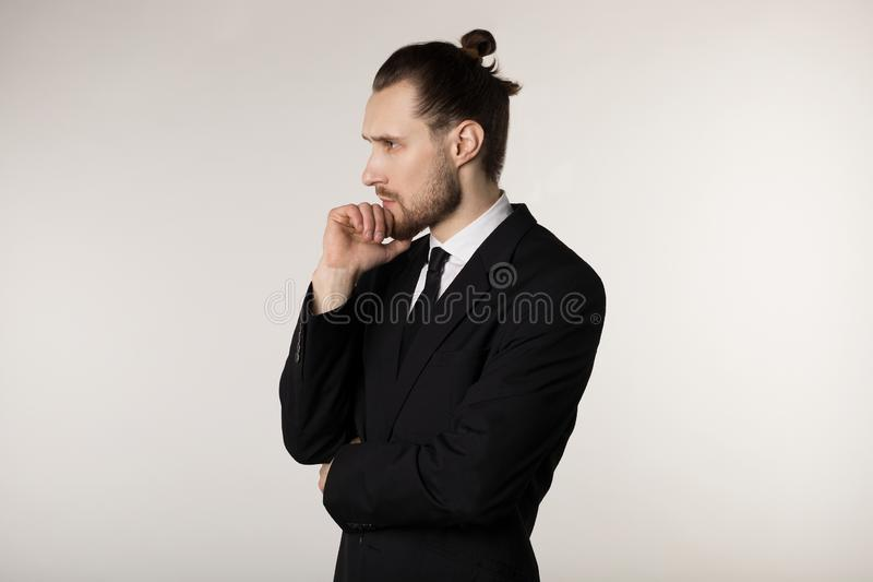 Bocznego widoku portret atrakcyjny młody biznesmen w czarnym kostiumu z elegancką fryzury mienia ręką na podbródku z obraz royalty free
