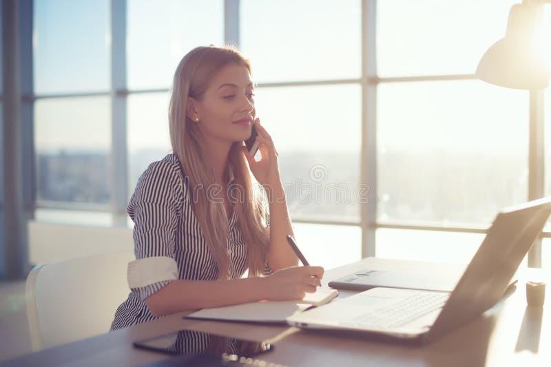 Bocznego widoku portret młody bizneswoman ma biznesu wezwanie w biurze, jej miejsce pracy, pisze puszkowi niektóre informaci fotografia stock
