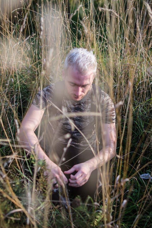 Bocznego widoku portret młody smutny atrakcyjny brodaty blondynka faceta obsiadanie na śródpolnej trawie obraz stock