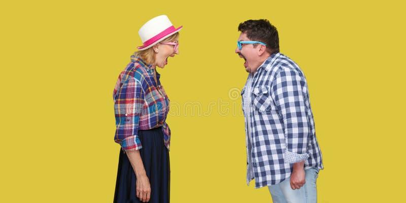 Bocznego widoku portret para przyjaciele, dorosły mężczyzna i kobieta w przypadkowej w kratkę koszulowej pozycji, do siebie i krz obrazy royalty free
