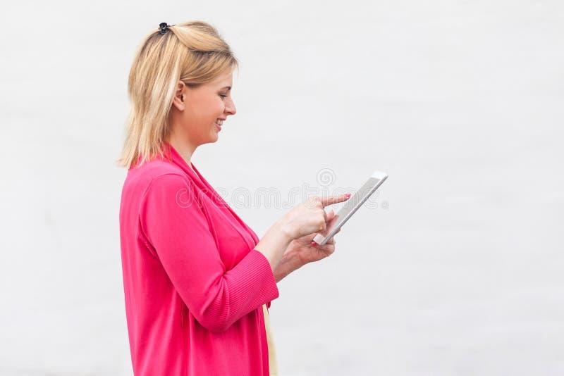 Bocznego widoku portret pomyślna bizneswoman młoda kobieta w różowej bluzki pozycji, używać informację na jej pastylce i szukając obraz royalty free
